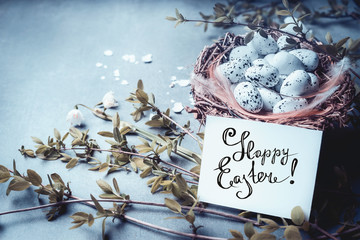 Happy Easter greeting card with lettering, nest with bird eggs and spring twigs and flowers. Blue toned