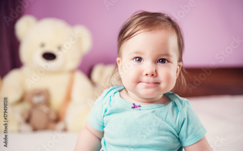 86c8f13746e2 Cute smiling little baby girl sitting on the bed with soft toys ...