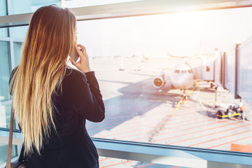 Young businesswoman talking on mobile phone waiting for her flight looking at planes through the window standing in departure zone at airport