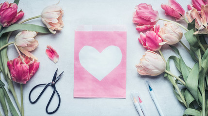 Lovely pastel color spring mock up with tulips, scissors , markers and pink pack paper bag  with heart , top view, flat lay