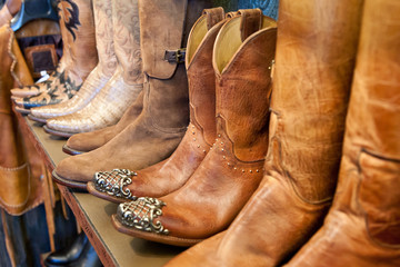 Cowboy boots on a shelf in a store aligned, closeup