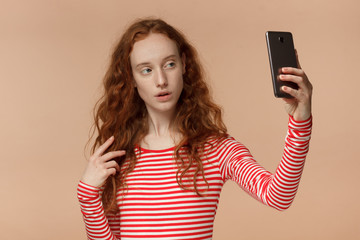 Portrait of attractive young redhead female using smartphone to take selfie pictures and smiling at camera