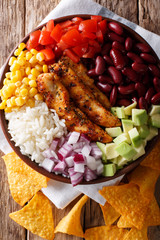 Burrito bowl with grilled chicken and vegetables close-up. Vertical top view