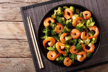 Stir frying shrimp with broccoli closeup. Horizontal top view