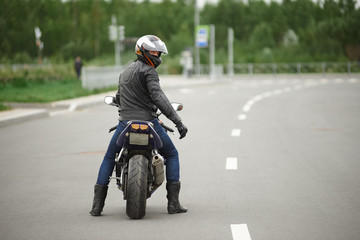 Sports, extreme, speed, adrenaline and determination concept. Rear view of stylish biker in leather clothes and safety helmet riding his motorcycle along empty high way, turning face to camera