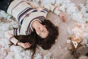 Pretty woman in handmade knitted sweater with scandinavian ornament in cozy winter decorations. artificial snow and lanterns, light garland