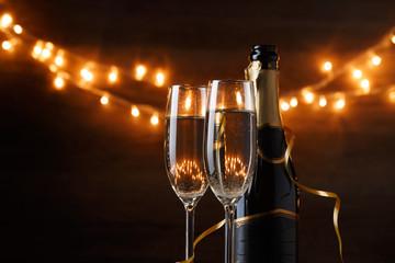 Festive photo of two wine glasses with wine, bottles, cork, burning garland