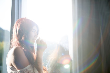 Long-haired pensive girl with cup of tea by window in room.