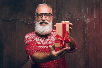 Senior bearded man holding gift box over dark background and looking at camera with smile  Santa Claus wishes Merry Christmas and a happy new year 2018!