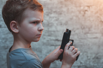 Boy with gun in hand against a brick wall,