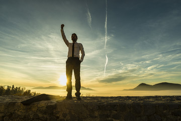 Triumphant businessman in white shirt standing outdoors with his fist raised
