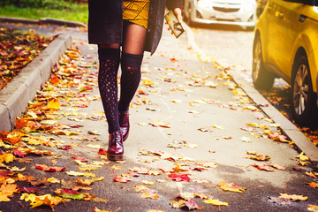 Young woman with smartphne in her hand walking on pavement/sidewalk covered with autumn leaves