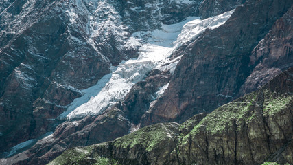 Close up view of a glacier passing through the grey rocky mountain..Summer in the Pennine Alps, Valle d'Aosta, Italy, Europe.