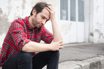 Man in troubles sitting next to an urban wall