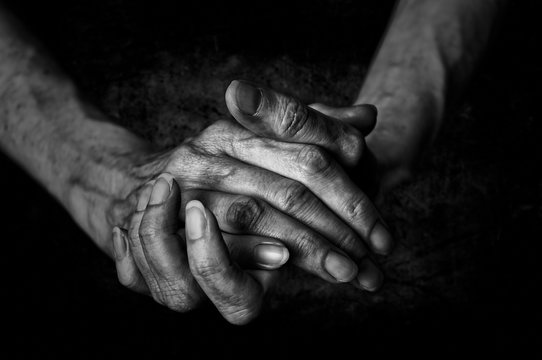 Black and White photo of senior woman hands on black background