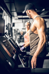 Attractive man running on treadmill and looking at girl