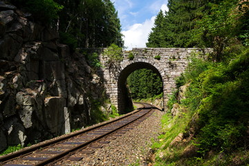Romantic stone bridge over railway in beautiful forest, Czech republic