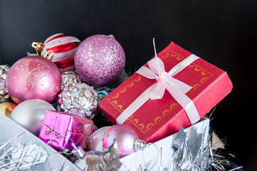 Gift tied with a pink ribbon in box with Christmas-tree toys