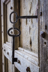 Old open wood door with steel heavy key in the hole