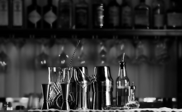 Set of bar accessories for making cocktails, located on the bar, behind is a shelving with liqueurs and strong alcohol.