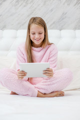 Teen girl using tablet pc at cozy home atmosphere on the bed