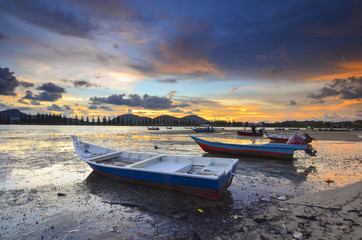 Fisherman boat on mud during lowtide with dramatic sunset at background.