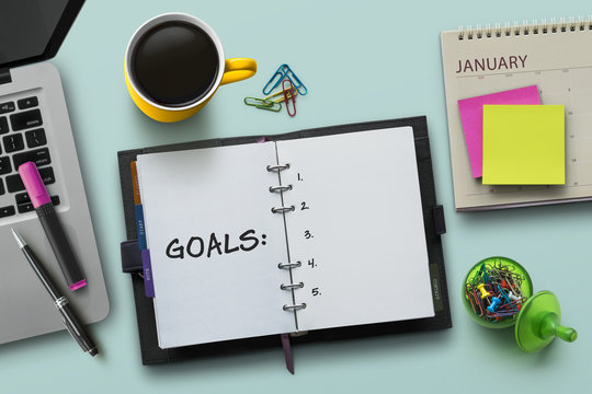 New Year goals, resolution or action plan concept. Notebook on table with laptop, calendar, coffee, plant and stationery. Flat lay (top view) notepad for input copy or text on turquoise background.