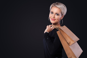 Black friday holiday. Happy blonde woman at shopping holding yellow bag isolated on black background.. Copy space for sale.