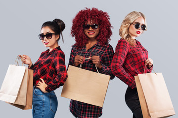 Three happy women in sunglasses. Afro american, asian and caucasian races. Shopping with isolated on gray background on black friday holiday. Concept for sale advertisement.