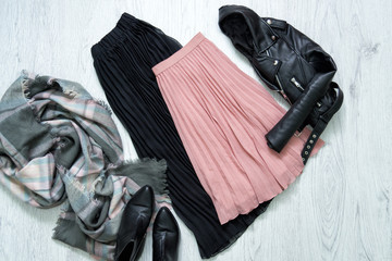 Black and pink skirt, jacket, scarf and boots. Fashionable concept