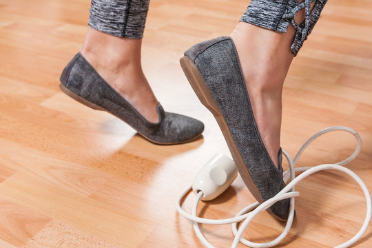 Closeup of woman's foot caught in electrical cord tripping over it at home