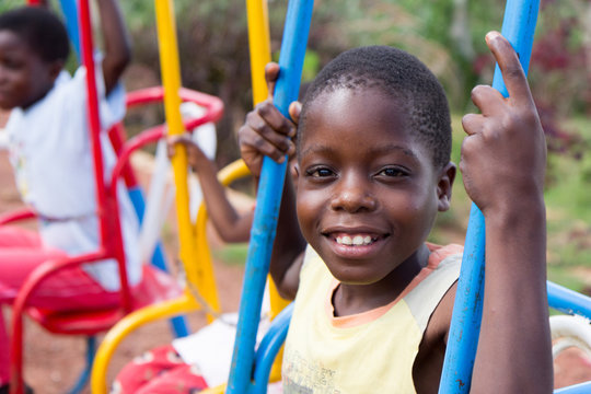 A smiling 13-year old Ugandan boy swinging on a colorful swing