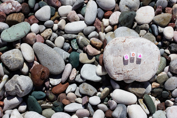 The word Goa on the pebbles on the sea shore