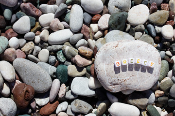 The word Greece on the pebbles on the sea shore