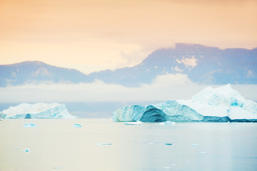 Big blue icebergs near the Saqqaq village at sunset, western Greenland