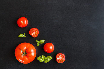 Fresh cherry tomatoes on a black chalkboard background with herb basil. Top view with copy space.