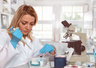 Young female tech or scientist loads liquid sample into test tubes