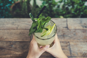 Top view image of hands holding a glass of iced lemon juice with mint leaves on wooden table baclground