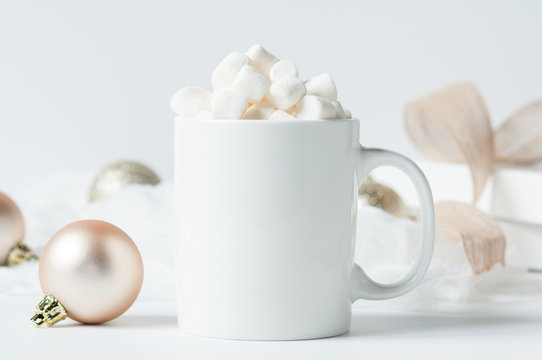 mug of hot chocolate with marshmallows surounded by Christmas decorations