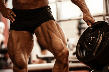 Close-up of bodybuilders muscular legs. Athlete man doing workout exercise in gym. Wall mural