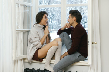 Couple sitting on the window sill at cold snowy day