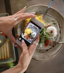 Young woman taking photo of delicious food with mobile phone at table