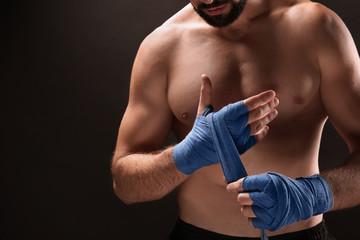 Male boxer applying wrist wraps on dark background