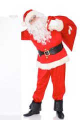 Santa Claus pushes blank white wall, advertisement banner with copy space while carrying on big bag. Isolated on white background. Full length portrait