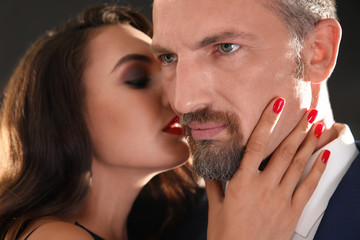 Woman with bright makeup kissing man