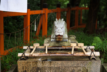 Water basin with an angry dragonhead as a fountain, Fushimi Inari Shrine, Kyoto, Japan