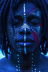 Portrait of a Sexy African man with traditional face paint and neon lighting