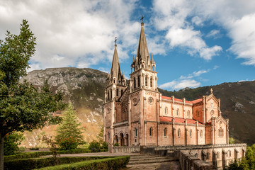 Basilica of Santa Maria la Real de Covadonga, Asturias, Spain, Europe. Beautiful church of touristic travel destination in autumn with a vibrant colorful sky and green natural forest with mountains.
