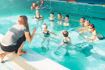 Instructor teaches children how to swim