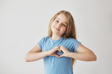 Beautiful blonde girl with light hair in blue t-shirt looking in camera with gentle smile, making heart gesture with hands, posing for school photoshoot.